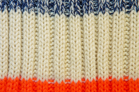 Close up on knit woolen fur texture. Color woven thread sweater or scarf as a background.