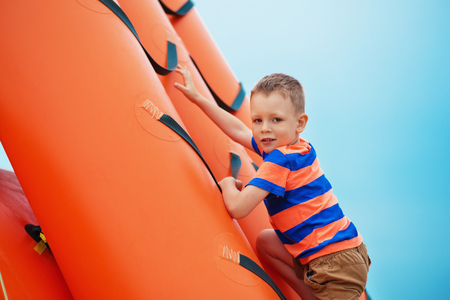 blowup: Little boy playing on an inflatable playground on the beach on a summer day.