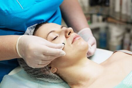 Beautician performs a needle mesotherapy treatment on a womans face Stock Photo