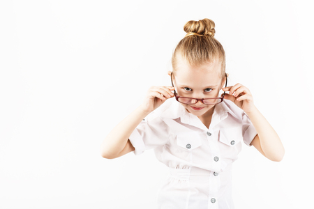Funny little girl wearing eyeglasses imitates a strict teacher against white background.  Little student Looking at camera.  School concept.  Back to School Stock Photo
