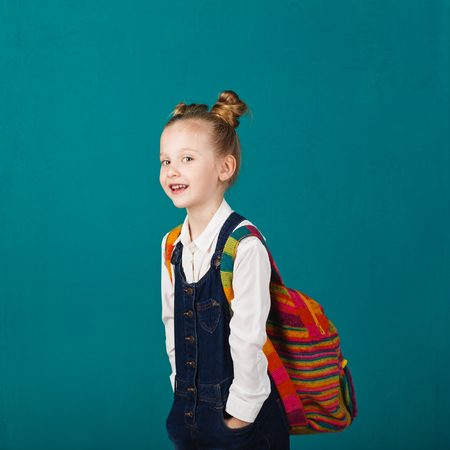 gesticulate: Funny smiling little girl with big backpack jumping and having fun against blue wall. Looking at camera. School concept. Back to School