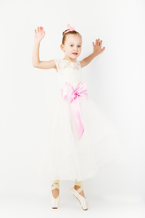 Beautiful ballet dancer isolated on white background. Slender little ballerina girl in white dress and in pointe shoes