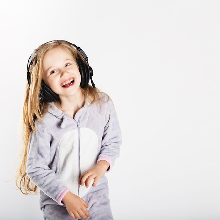 Cute little girl in headphones is using a smartphone, looking at camera and having fun at home. Day off, holiday, day of rest, free, off-time Stock Photo