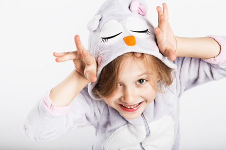 Funny little girl in pajamas jumping and having fun in bed at home. Pajama party, Day off, holiday, day of rest, free, off-time