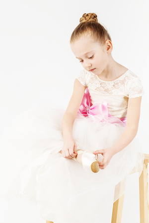 A small ballerina dresses or takes off her pointe isolated on white background. Slender little ballerina girl in white dress and in pointe shoes Stock Photo