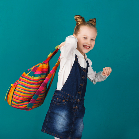 Funny smiling little girl with big backpack jumping and having fun against blue wall. Looking at camera. School concept. Back to School