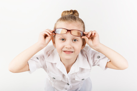 Closeup portrait of little girl wearing eyeglasses imitates a strict teacher against white background.  Little student Looking at camera.  School concept.  Back to School
