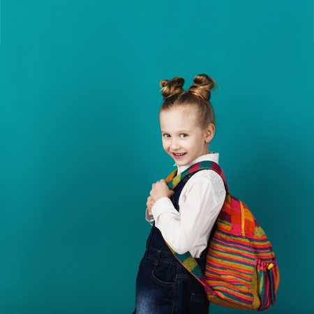 Beautiful smiling little girl with big backpack standing against blue wall. Looking at camera. School concept. Back to School