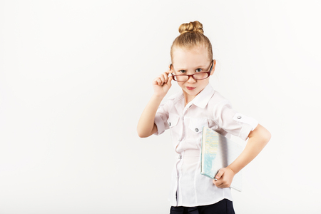 Funny little girl wearing eyeglasses imitates a strict teacher against white background.  Little student holding books.  Looking at camera.  School concept.  Back to School Stock Photo