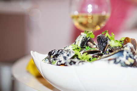 Steamed mussels in cheese sauce. Mussels in shells in the bowl with white wine on the table.
