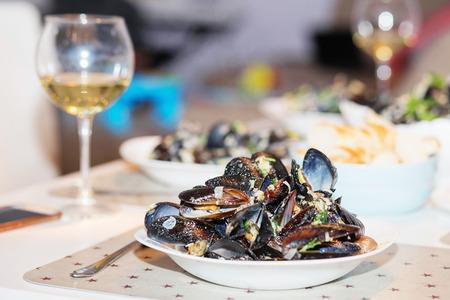 almeja: Mejillones al vapor en salsa de queso. Mejillones en conchas en el recipiente con vino blanco en la mesa.