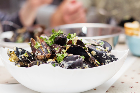 mussel: Steamed mussels in cheese sauce. Mussels in shells in the bowl with white wine on the table.