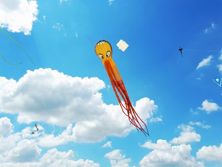 Big kite flying in a blue sky. Kites of various shapes. kiting