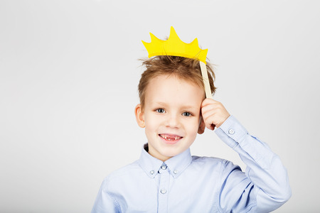 Portrait of a cute little school boy with yellow paper crown against a white background. Cheerful smiling Kid with funny photo props. Back to School. Childs toothless mouth