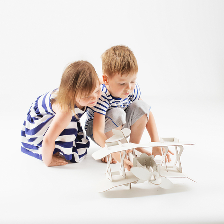 Little Children playing with paper toy airplane sitting on the floor against a white background. Small Kids dreaming of becoming a pilot. Childhood. Fantasy, imagination.