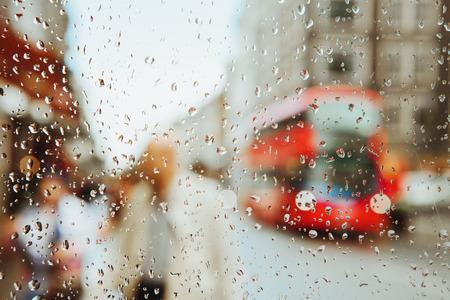 Regendruppel op glas en rode Londen buslichten wazige achtergrond.