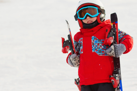 Little cute boy with skis and a ski outfit. Little skier in the ski resort. Winter holidays. Skiing Stock Photo
