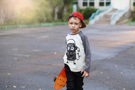 skate park: Little urban boy with a penny skateboard. Young kid riding in the park on a skateboard. City style. Urban kids. Child learns to ride a penny board