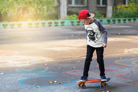 Little urban boy with a penny skateboard. Young kid riding in the park on a skateboard. City style. Urban kids. Child learns to ride a penny board