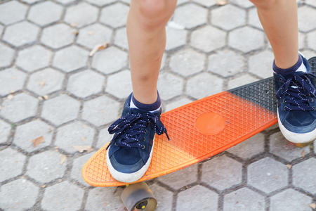 Little boy standing on a orange skateboard outdoors. Closeup image of childrens feet at skateboard. Kids feet in sneakers on a skateboard. Boy rides on the asphalt on a plastic skateboard