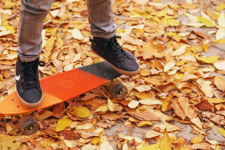 Little boy standing on a orange skateboard outdoors. Closeup image of childrens feet at skateboard. Kids feet in sneakers on a skateboard. A boy skating in an autumn park