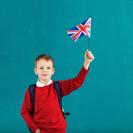 School Holidays United Kingdom (UK). Little schoolboy with national flag of the United Kingdom. School concept. Back to School Foto de archivo