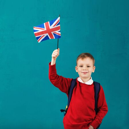 School Holidays in Great Britain. Little schoolboy with national flag of the United Kingdom having fun against the blue wall. English for children concept. Back to School