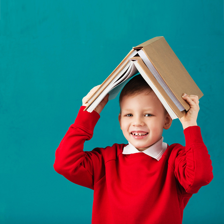 Cheerful smiling little school boy in red sweatshirt holding big heavy books on his head against turquoise wall. Looking at camera. School concept. Back to School Stock Photo