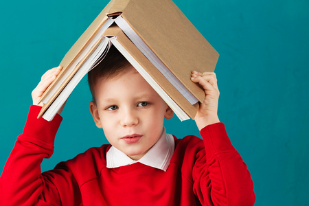 Cheerful smiling little school boy with big heavy books on his head having fun against turquoise wall. Looking at camera. School concept. Back to School Stock Photo