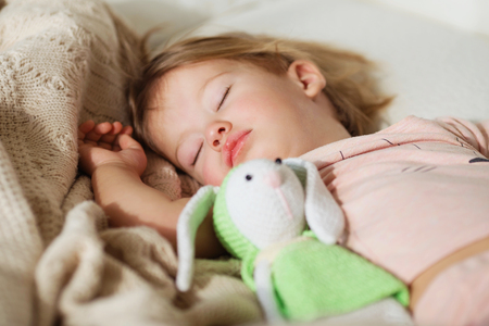 slumber: Sleeping little girl. Carefree sleep little baby with a soft toy on the bed. Close-up portrait of a beautiful sleeping child on knitted blanket. Sweet dreams Stock Photo
