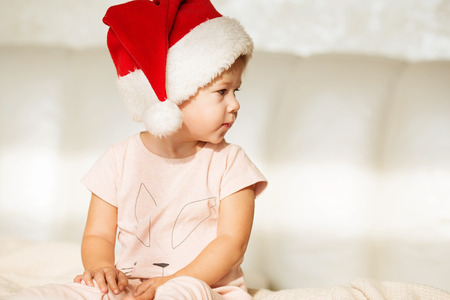 Little girl in santa hat. half-face Portrait of beautiful baby girl in christmas clothing