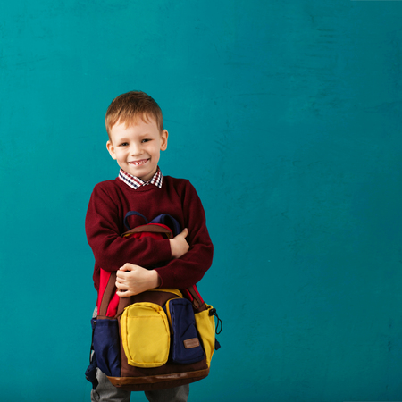 Cheerful thoughtful little school boy in school uniform with big backpack standing against blue wall. Looking at camera. School concept. Back to School
