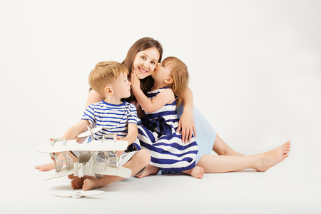 Portrait of a happy mother and her two little children - boy and girl. Happy family against a white background. Little kids kissing mother. Children with toys. Foto de archivo