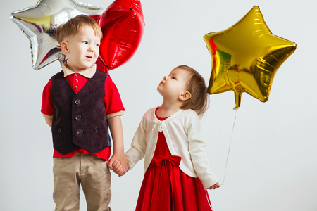 Children holding a star shaped balloons. Happy children playing with colorful shiny foil balloons against a white background