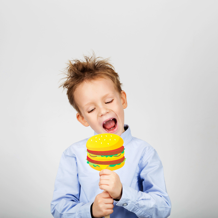 Cute little school boy with fake paper burger against a white background. Cheerful smiling Kid with funny photo props. unhealthy food concept. Back to School. Childs toothless mouth
