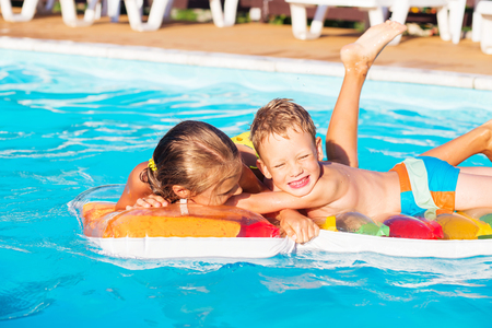 Little children playing and having fun in swimming pool with air mattress. Kids playing in water. Swimming concept. Boy and girl swim in resort pool during summer vacations Standard-Bild