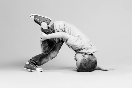 break dance kids. little break dancer showing his skills in dance studio. Hip hop dancer boy performing over studio background. Black and white photography