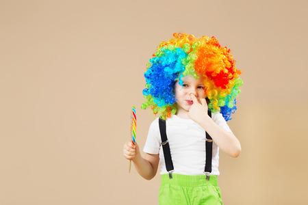 Glücklicher Clownjunge in der großen bunten Perücke. Lass uns Party machen! Lustiger Kinderclown. 1 Aprilscherz Konzept. Kind essen Lutscher. Finger in der Nase. In der Nase pflücken.