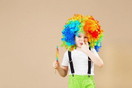Happy clown boy in large colorful wig. Let's party! Funny kid clown. 1 April Fool's day concept. child eating lollipop. Finger in the nose. Picking in the nose.