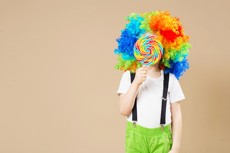 Happy clown boy in large colorful wig. Lets party! Funny kid clown. 1 April Fools day concept. Portrait of a child eating lollipop. Birthday boy.