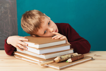 tired school boy asleep on books. little student sleeping on textbooks. Child in school uniform lies on the table with big pile of books against blue wall. School concept. Back to school Stock Photo