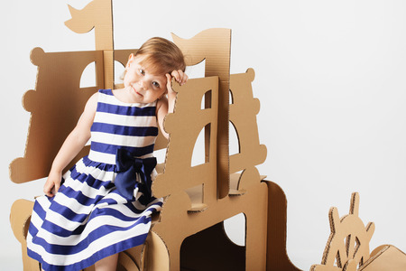 Cute  Little girl wearing striped dress in a marine style playing with cardboard ship on white background. Happy children. Childhood. Fantasy, imagination. Reklamní fotografie