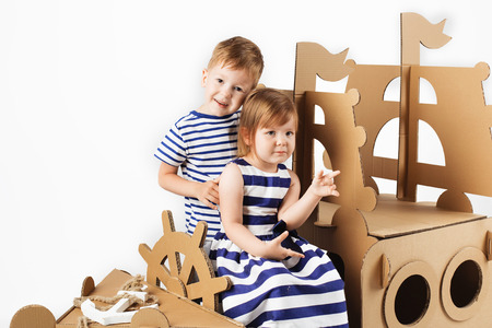 Little kids playing with cardboard ship on white background. Happy children. Childhood. Fantasy, imagination. Reklamní fotografie