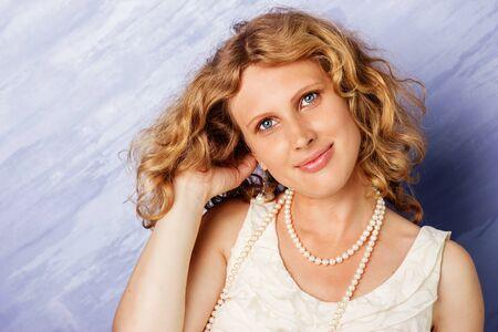 Beautiful blue-eyed curly blonde in front of a blue background.
