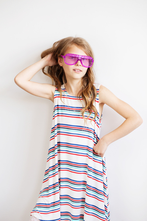 Lovely little girl in a striped dress with funny party plastic striped sunglasses in front of white background. Happy kids. Summer emotions