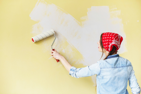 Beautiful girl in red Headband painting the wall with paint roller. Portrait of a young beautiful woman painting wall in her new apartment Stock Photo