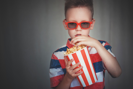 Young boy watch a movie in 3D glasses at the cinema or at home. Little kid eat popcorn over gray background. Home theater. Cute Child in vintage cinema eyeglasses. Entertainment concept. Stock Photo