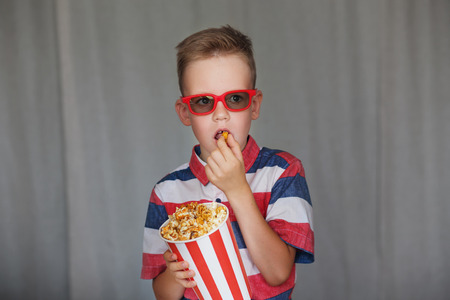 Home theater. Cute Child in vintage cinema eyeglasses. Entertainment concept. Young boy watch a movie in 3D glasses at the cinema or at home. Little kid eat popcorn over gray background.
