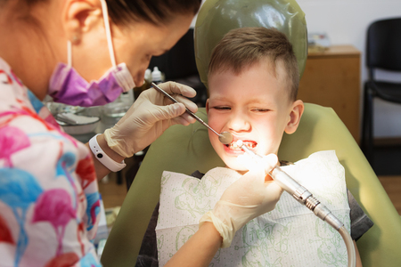 A little boy at a dentist's reception in a dental clinic. Children's dentistry, Pediatric Dentistry. A female stomatologist