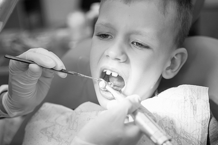 A little boy at a dentists reception in a dental clinic. Childrens dentistry, Pediatric Dentistry. Blac and white retro style photography. Oral health and hygiene
